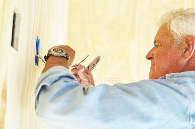 Senior man working on electrical wiring in house. — Stock Photo