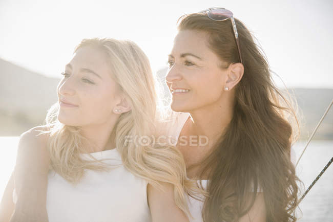 Mother with teenage daughter on sailboat at lake. — Stock Photo