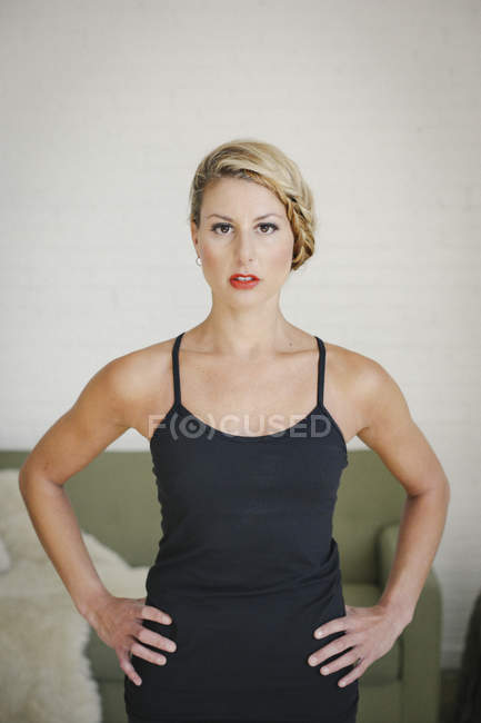 Blonde woman in black leotard standing with hands on hips and looking in camera. — Stock Photo