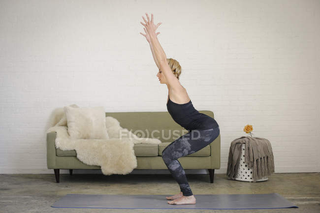 Woman squatting down with arms raised on yoga mat in room. — Stock Photo