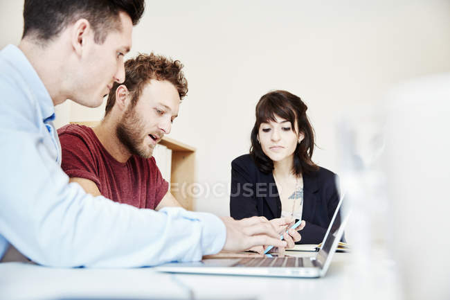 Colleagues sitting at table at business meeting and using laptop computer. — Stock Photo