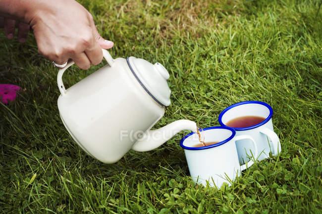 Weibliche Hand Gießen Tee aus Topf in Tassen auf grünen Rasen. — Stockfoto