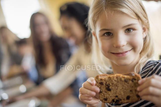 Elementary menina idade segurando biscoito na cozinha . — Fotografia de Stock