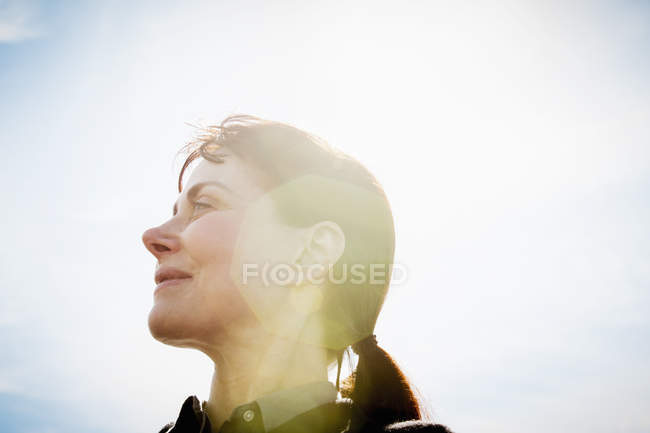 Low angle view of mature woman looking away in sunlight. — Stock Photo