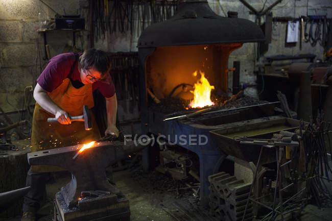 Female blacksmith striking red hot metal on anvil inside workshop. — Stock Photo