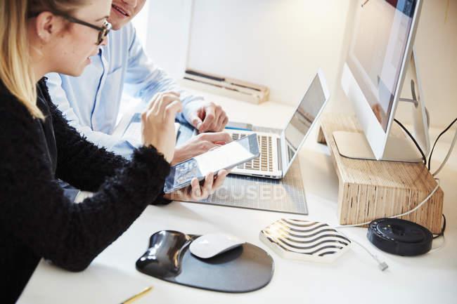 Due persone che lavorano insieme su tablet, computer portatile e monitor . — Foto stock