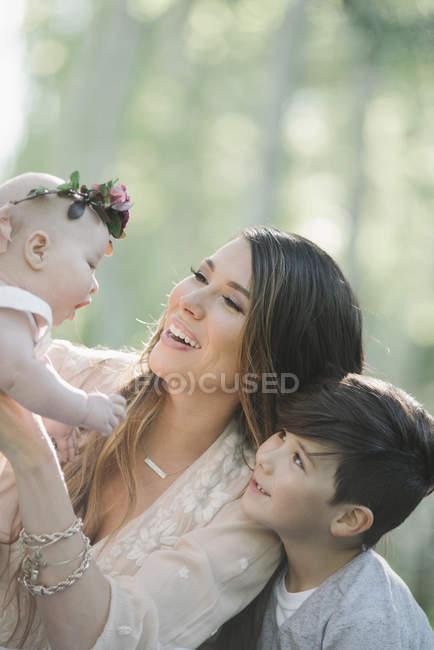 Улыбающаяся мать носит девочку с цветочным венком с сыном на открытом воздухе . — стоковое фото