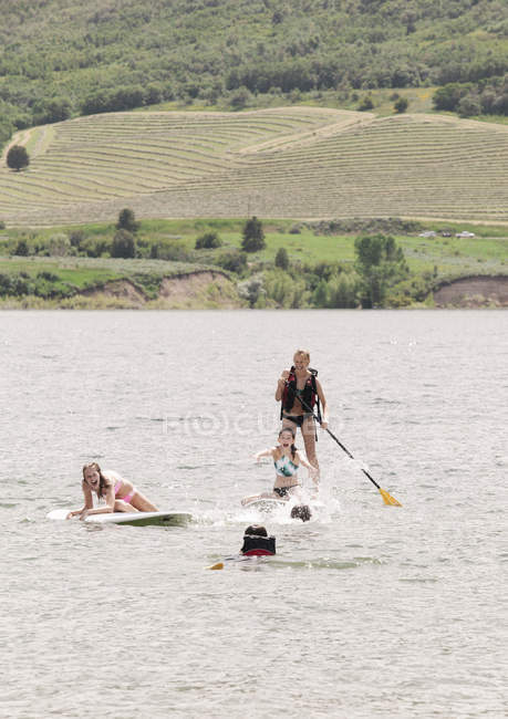 Дівчаток-підлітків встати з веслом серфінгу на воді озера. — стокове фото