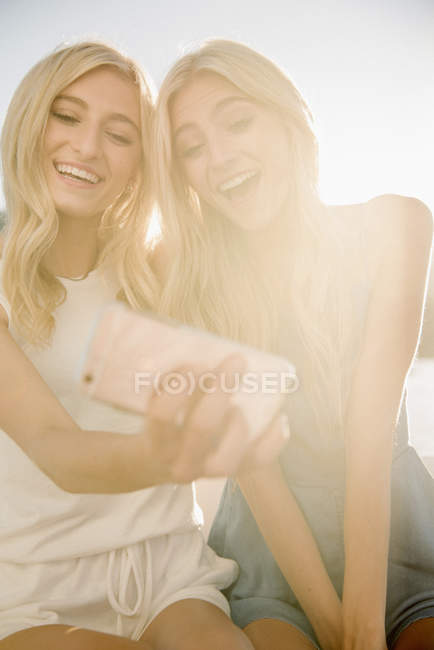 Two blonde teenage girls taking selfie with smartphone against soft light. — Stock Photo