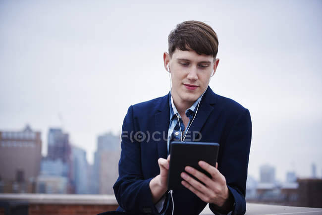 Young businessman with earphones standing on rooftop and using digital tablet. — Stock Photo