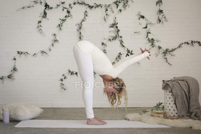 Blonde woman in white leotard and leggings bending down and stretching on yoga mat. — Stock Photo