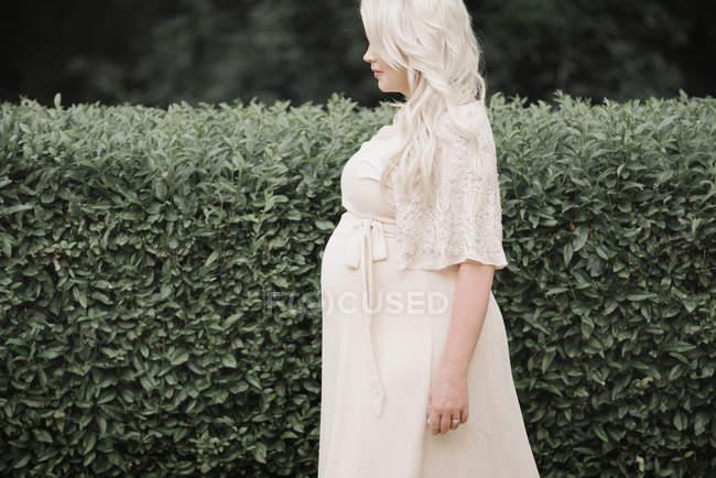 Vista laterale della donna incinta in abito bianco in piedi nel giardino verde . — Foto stock