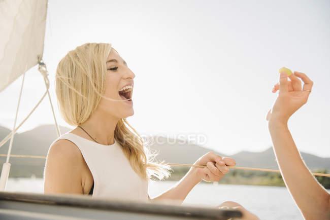 Blonde Teenager-Mädchen lachen mit Mund offen auf Segelboot. — Stockfoto