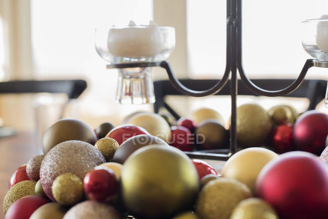 Close-up of colorful Christmas ornaments and candles in candle holder on table. — Stockfoto