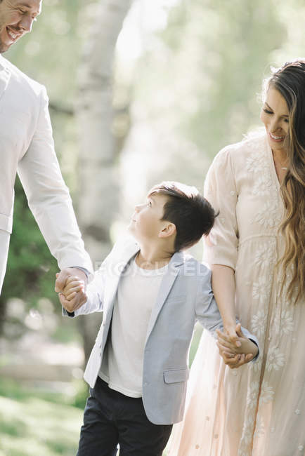 Father, mother and son walking and holding hands in park. — Stock Photo