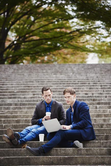 Due giovani uomini seduti sui gradini del parco e utilizzando il computer portatile insieme . — Foto stock