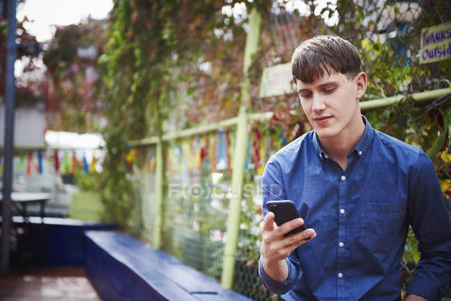 Young man sitting in city park and looking down at smartphone. — Stock Photo