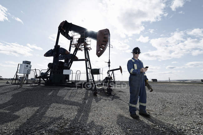 Man in overalls and hard hat at pump jack in open ground at oil extraction site. — Stock Photo