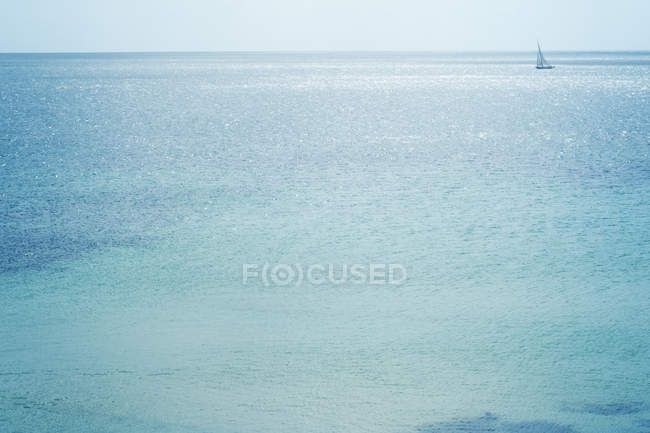 Distant view of sailing boat on shimmering blue sea. — Stock Photo