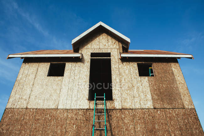 House under construction with ladder leading to large window, low angle view. — Stock Photo