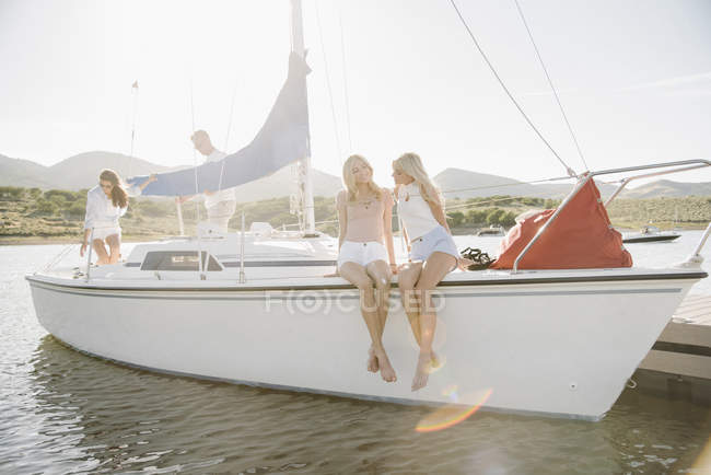 Teenage sisters sitting with parents on sailboat on lake. — Stock Photo