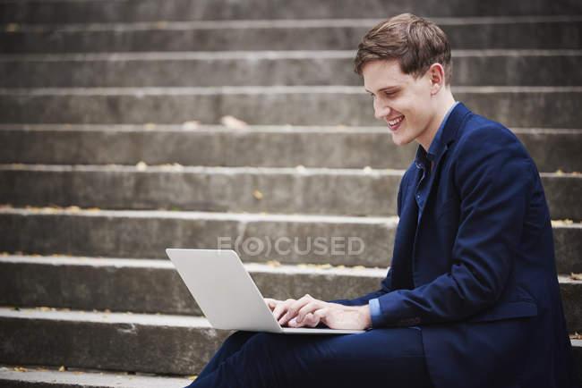 Joven sentado en los escalones de la ciudad y trabajando en el portátil . - foto de stock