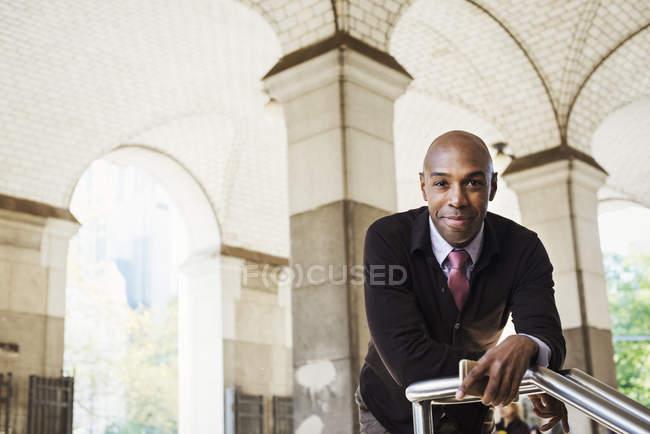 Empresario en traje apoyado en barandilla bajo techo arqueado en la calle y mirando en cámara . - foto de stock