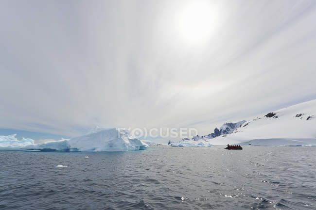 Group of people in rubber boat near iceberg offshore in Antarctic. — Stock Photo