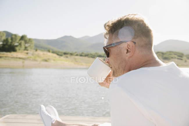 Hombre sentado en el embarcadero del lago y bebiendo de la taza de café . - foto de stock