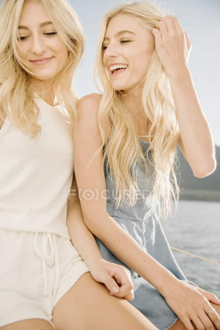 Portrait of two blonde sisters laughing on sailboat on lake. — Stock Photo