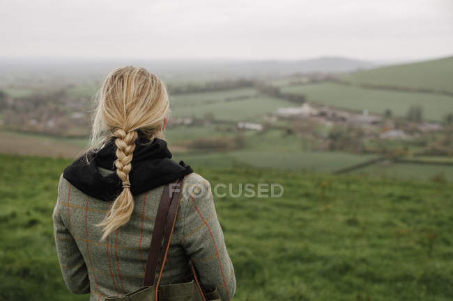 Rear view of woman standing in hilltop and looking at view. — Stock Photo