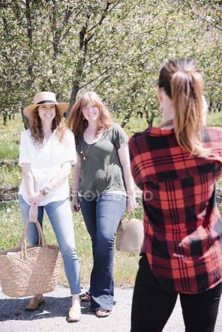 Задній вид жіночий фотограф, зйомки в жінок в районі orchard влітку. — стокове фото