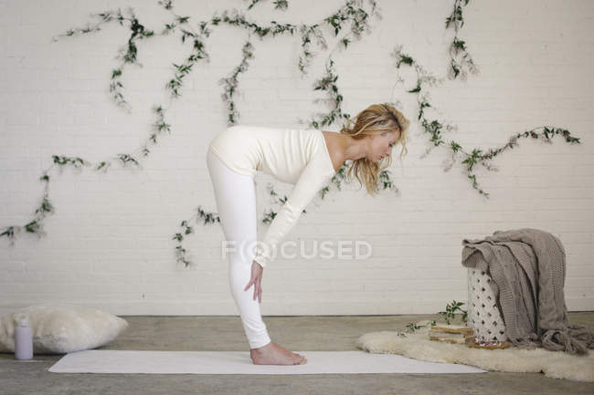 Blonde woman in white leotard and leggings bending forwards on yoga mat. — Stock Photo