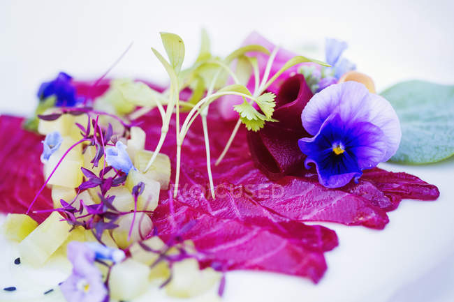 Carpaccio and garnish of fresh pea shoots and edible flowers on white plate. — Stock Photo