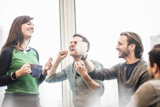 Colleagues laughing and raising coffee cups at break. — Stock Photo
