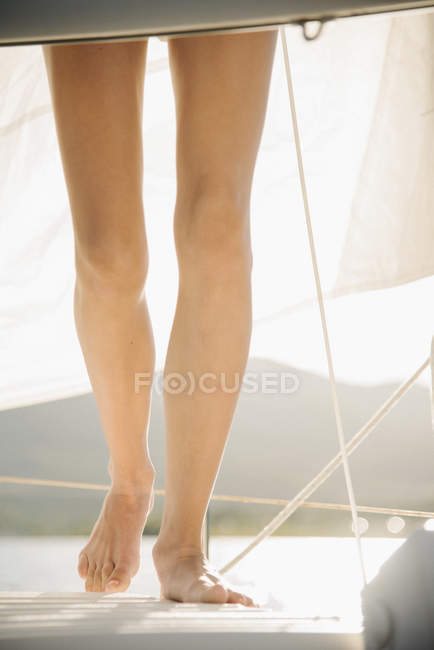 Ausgeschnittene Ansicht eines Teenagers, der barfuß auf einem Segelboot steht. — Stockfoto