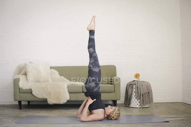 Woman doing shoulderstand on yoga mat in room. — Stock Photo