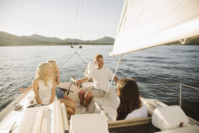 Mature parents and teenage daughters relaxing on sailboat on lake. — Stock Photo