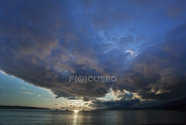 Sunset and cloudscape over calm sea surface. — Stock Photo