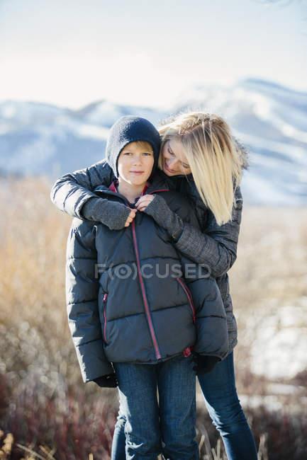 Frau umarmt Sohn in Jacke und Woolly Hut im freien — Stockfoto