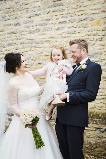 Mariée et marié couple tenant préscolaire demoiselle d'honneur . — Photo de stock