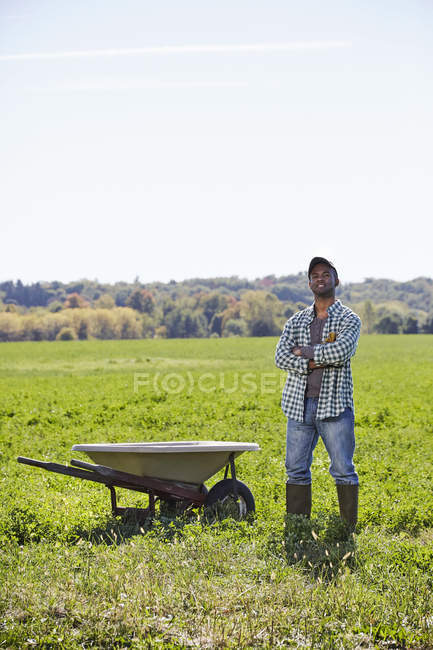 Mid adult man with arms crossed standing in crop field next to wheelbarrow. — Stock Photo