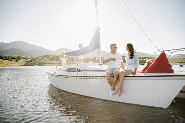 Мужчина и женщина, сидя на яхте с девочек-подростков в фоновом режиме — стоковое фото