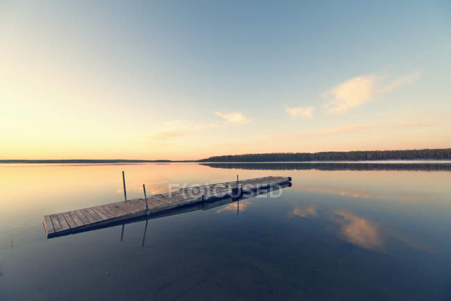 Quai en bois flottant sur l'eau calme plate du lac au coucher du soleil . — Photo de stock