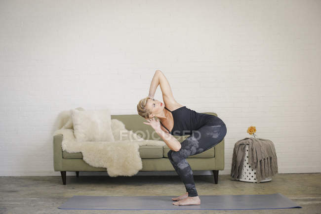 Blonde woman twisting and squatting down with arms behind head. — Stock Photo