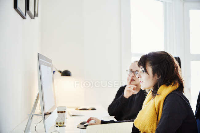 Two women sharing computer and discussing graphic on screen. — Stock Photo