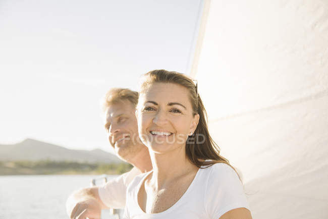 Man and woman on sailboat smiling and looking in camera, portrait. — Stock Photo