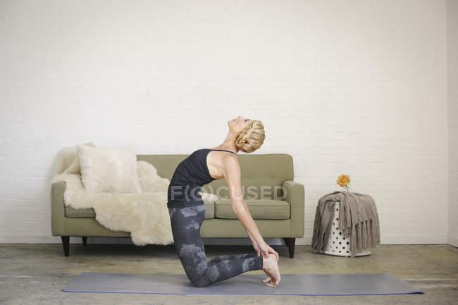 Blonde Frau kniend auf Yoga-Matte und biegen nach hinten — Stockfoto