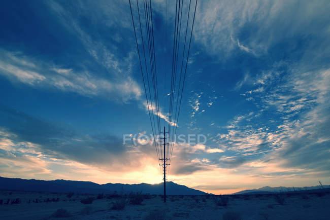 Линии электропередач на полюсе тянутся на расстояние в горном ландшафте . — стоковое фото
