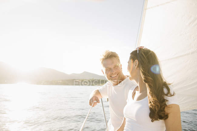 Man and woman standing and smiling while looking at each other on sailboat. — Stock Photo